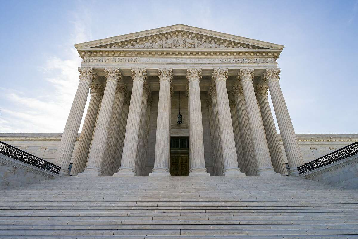 FILE - In this June 17, 2019 file photo, The Supreme Court in Washington. A divided Supreme Court is allowing the Trump administration to put in place a policy connecting the use of public benefits with whether immigrants could become permanent residents. (AP Photo/J. Scott Applewhite)