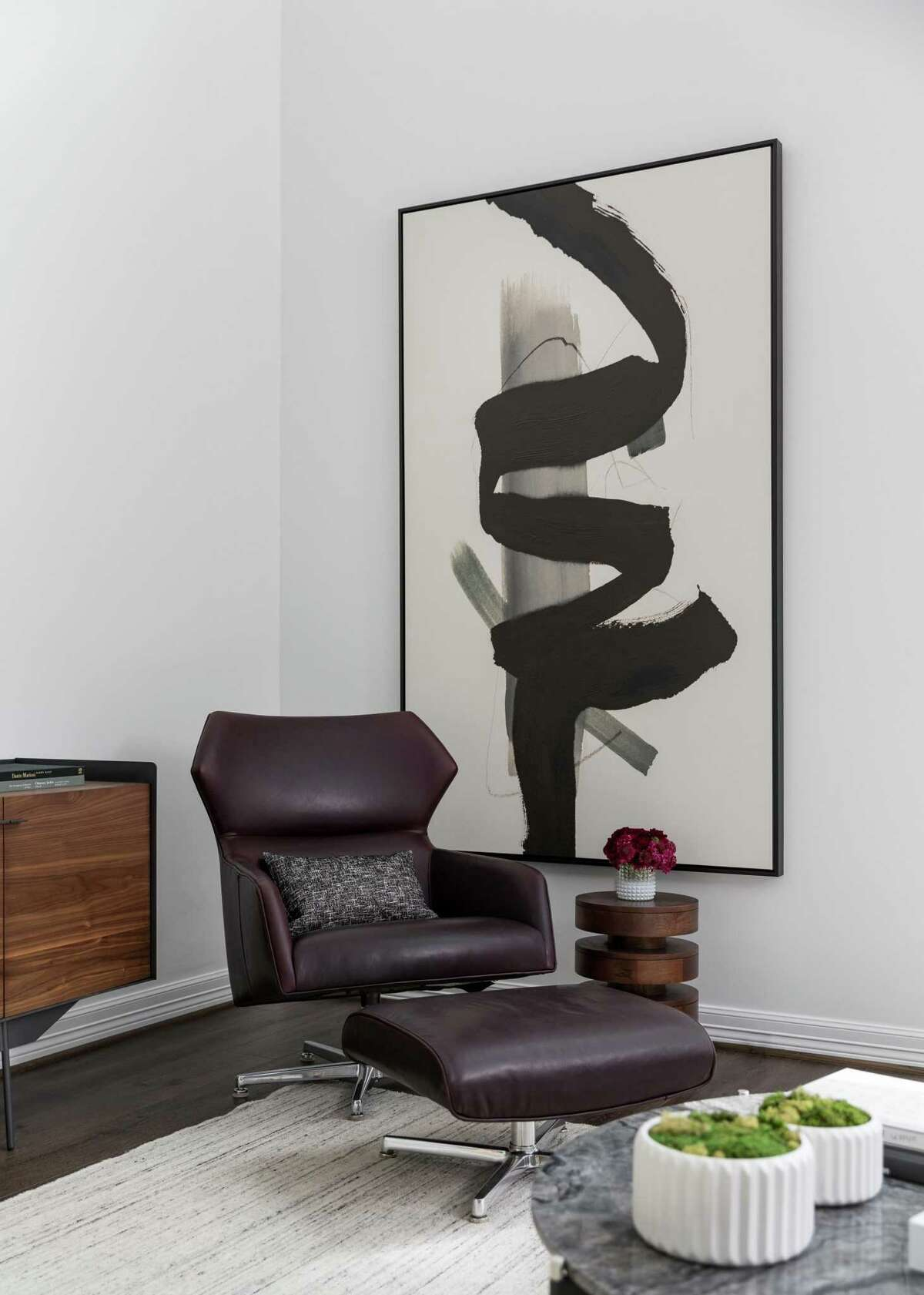 One corner of the living room has a deep burgundy chair and ottoman in front of a large-scale abstract painting.