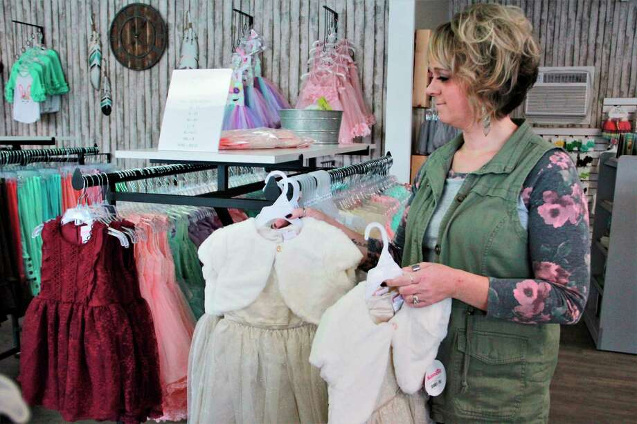 Everleigh Ray's Piggies and Pearlsowner Angela Gross stocks items during a typical work day. According to Gross, the children's boutique will be offering more dress options as the annual Daddy Daughter Dance comes up Feb. 21. (Pioneer photo/Alicia Jaimes)