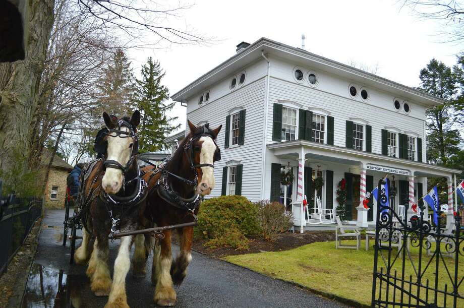 """Horses Ben and Sampson bring the carriage out of the driveway at the """"Jingle Bell Rock: Family Day with Santa"""" at the then named Westport Historical Society on Saturday, Dec. 15, 2018, in Westport, Conn. Photo: Jarret Liotta /For Hearst Connecticut Media / Westport News Freelance"""