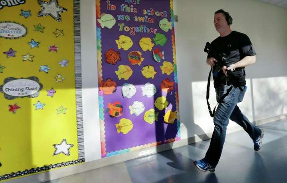 In this Associated Press file photo, a police officer portrays an active shooter with an assault rifle loaded with dummy rounds. The scene depicted is not related to Bethalto Community School District's new protection plan and efforts. Photo: AP Photo/Charles Krupa