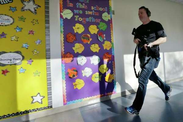 In this Associated Press file photo, a police officer portrays an active shooter with an assault rifle loaded with dummy rounds. The scene depicted is not related to Bethalto Community School District's new protection plan and efforts.