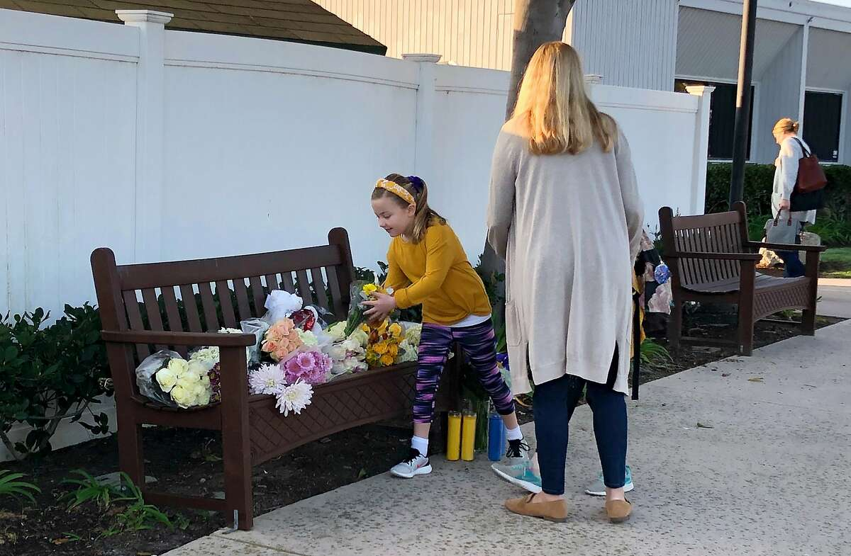 Flowers and messages are placed in front of Harbor Day School, a private elementary school in Corona Del Mar, Calif., Monday, Jan. 27, 2020. Christina Mauser, a girls basketball coach at the school, was among those killed in the helicopter crash that took the lives of former Lakers star Kobe Bryant and seven others Sunday. (AP Photo/Amy Taxin)