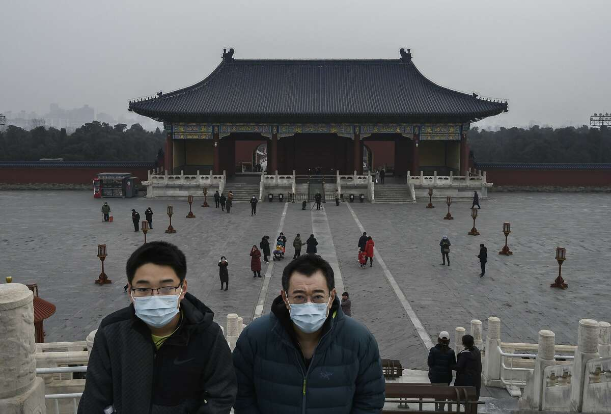 Chinese visitors wear protective masks as they tour the grounds of the Temple of Heaven, which remained open during the Chinese New Year and Spring Festival holiday on January 27, 2020 in Beijing, China. The number of cases of a deadly new coronavirus rose to over 2700 in mainland China Sunday as health officials locked down the city of Wuhan last week in an effort to contain the spread of the pneumonia-like disease which medicals experts have confirmed can be passed from human to human. In an unprecedented move, Chinese authorities put travel restrictions on the city which is the epicentre of the virus and neighbouring municipalities affecting tens of millions of people. The number of those who have died from the virus in China climbed to at least 80 on Monday and cases have been reported in other countries including the United States, Canada, Australia, France, Thailand, Japan, Taiwan and South Korea.Due to concerns over the spread of the virus, the Beijing government closed many popular attractions such as the Forbidden City and sections of the Great Wall among others. (Photo by Kevin Frayer/Getty Images)
