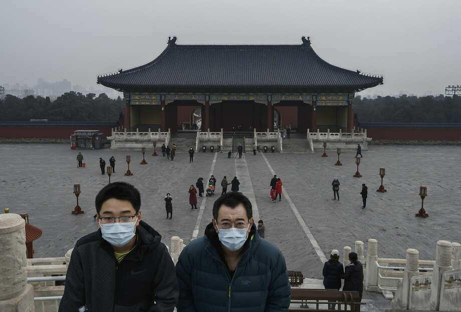 Chinese visitors wear protective masks as they tour the grounds of the Temple of Heaven, which remained open during the Chinese New Year and Spring Festival holiday on January 27, 2020 in Beijing, China. The number of cases of a deadly new coronavirus rose to over 2700 in mainland China Sunday as health officials locked down the city of Wuhan last week in an effort to contain the spread of the pneumonia-like disease which medicals experts have confirmed can be passed from human to human. In an unprecedented move, Chinese authorities put travel restrictions on the city which is the epicentre of the virus and neighbouring municipalities affecting tens of millions of people. The number of those who have died from the virus in China climbed to at least 80 on Monday and cases have been reported in other countries including the United States, Canada, Australia, France, Thailand, Japan, Taiwan and South Korea.Due to concerns over the spread of the virus, the Beijing government closed many popular attractions such as the Forbidden City and sections of the Great Wall among others. (Photo by Kevin Frayer/Getty Images) Photo: Kevin Frayer, Getty Images