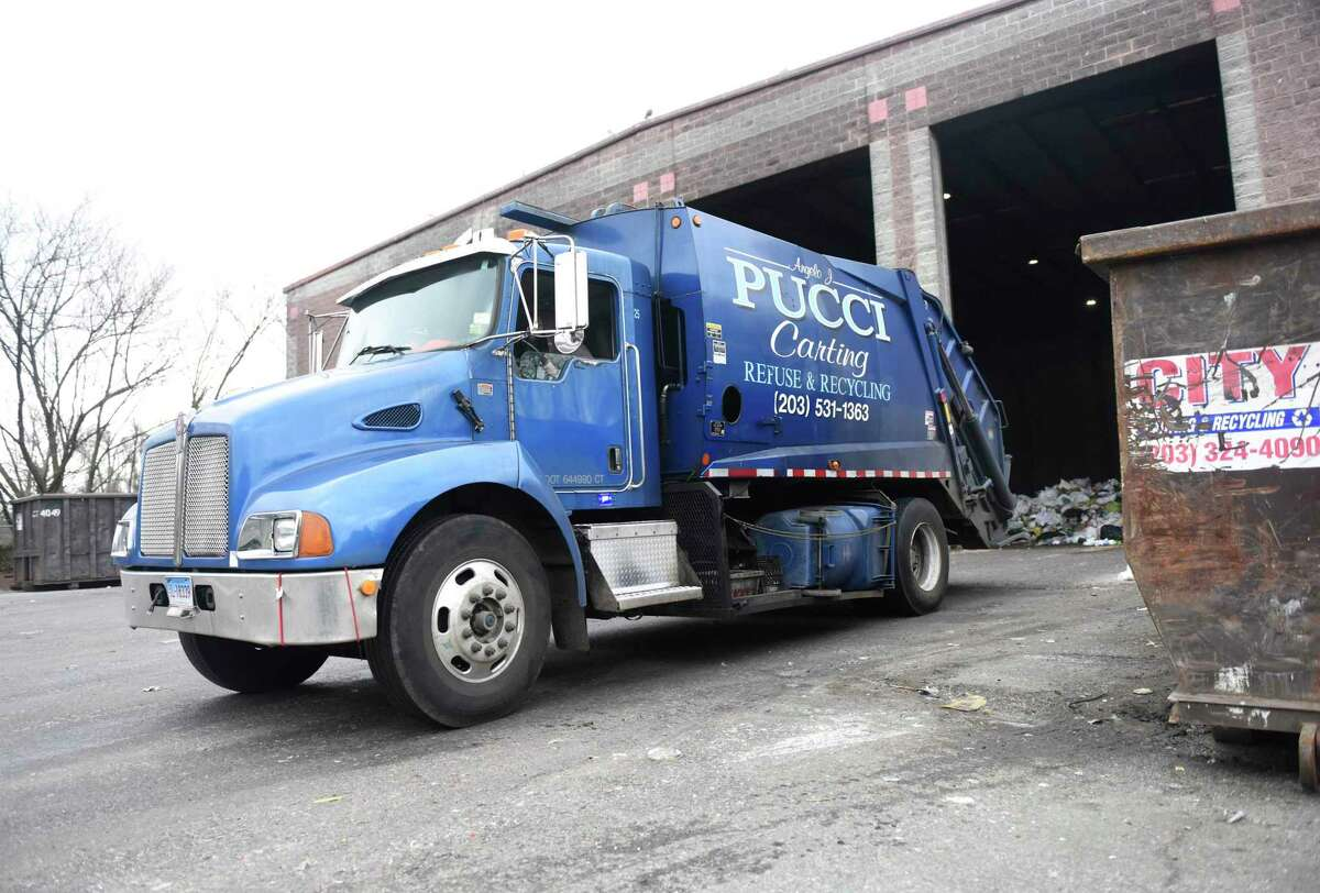 Trucks dump trash in the commercial dumping bay at the Holly Hill Transfer Station in Greenwich, Conn. Monday, Jan. 27, 2020.