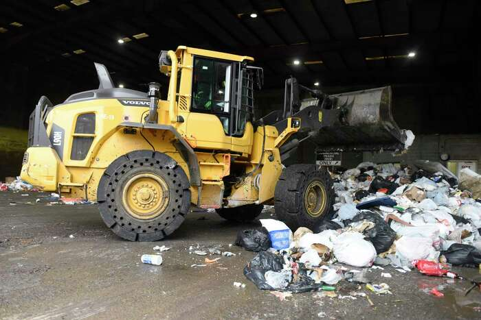 Equipment compacts trash in the commercial dumping bay at the Holly Hill Transfer Station in Greenwich, Conn. Monday, Jan. 27, 2020.