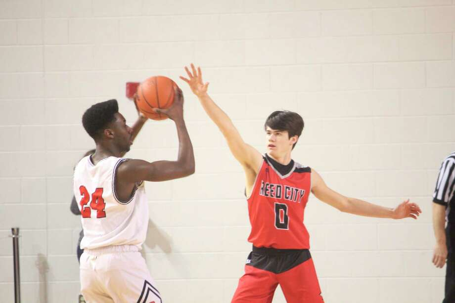 Big Rapids' Jamal Strickland (left) protects the ball against Reed City's Landen Tomaski (0) in recent action. (Pioneer photo/John Raffel)