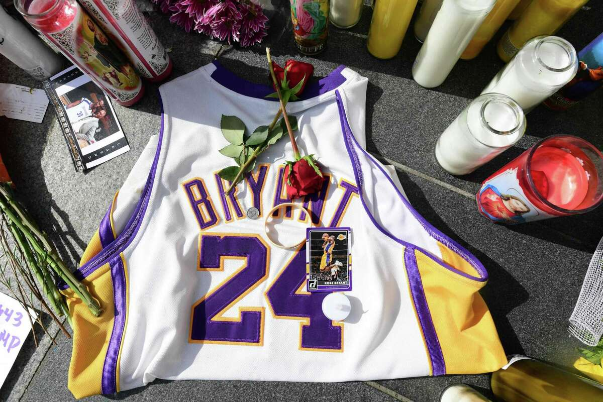 Fans place flowers, candles and memorabilia for NBA legend Kobe Bryant outside the Staples Center in Los Angeles, California on January 27, 2020. - Nine people were killed in the helicopter crash which claimed the life of NBA star Kobe Bryant and his 13 year old daughter, Los Angeles officials confirmed on Sunday. Los Angeles County Sheriff Alex Villanueva said eight passengers and the pilot of the aircraft died in the accident. The helicopter crashed in foggy weather in the Los Angeles suburb of Calabasas. Authorities said firefighters received a call shortly at 9:47 am about the crash, which caused a brush fire on a hillside. (Photo by FREDERIC J. BROWN / AFP) (Photo by FREDERIC J. BROWN/AFP via Getty Images)