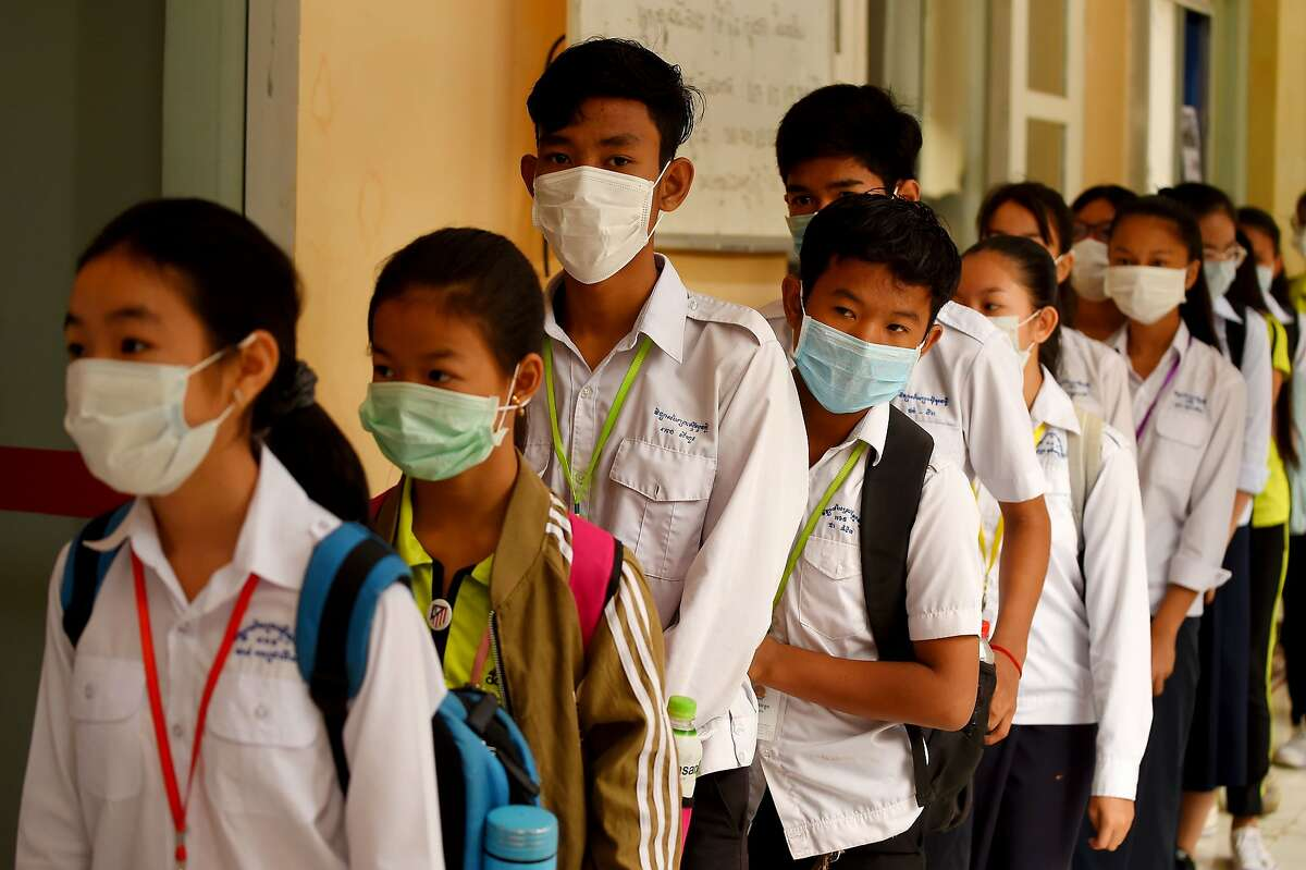 Mask-clad students line up to disinfect their hands with an alcohol solution before entering class at a school in Phnom Penh on January 28, 2020. - Cambodia's health ministry reported the country's first case of the deadly coronavirus on January 27. The virus, which can cause a pneumonia-like acute respiratory infection, has in a matter of weeks killed more 106 people and infected more than 4,000 in China, while cases have been identified in more than a dozen other countries. (Photo by TANG CHHIN Sothy / AFP) (Photo by TANG CHHIN SOTHY/AFP via Getty Images)