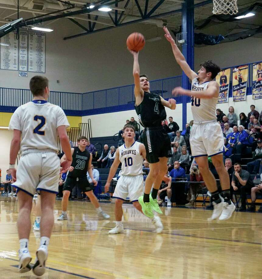 Pine River's Jayce Methner goes for a layup, while Carter Veldkamp of Morley Stanwood tries to block the attempt during Monday night's game at MSHS. (Pioneer photo/Joe Judd)