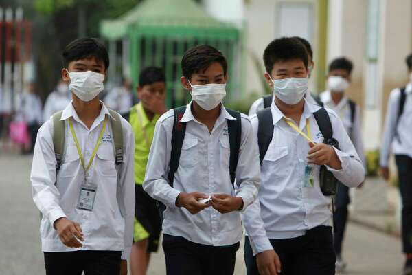 Students wear masks to avoid the contact of coronavirus at a high school in Phnom Penh, Cambodia, Tuesday, Jan. 28, 2020. China on Tuesday reported 25 more deaths from a new viral disease, as the U.S. government prepared to fly Americans out of the city at the center of the outbreak.