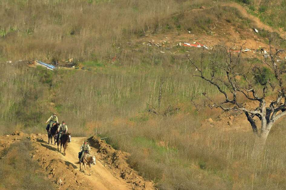 Sheriff's deputies on horseback leave the scene of a helicopter crash, Monday, Jan. 27, 2020, that killed former NBA basketball player Kobe Bryant, his 13-year-old daughter, Gianna, and seven others, in Calabasas, Calif., on Sunday.