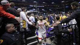 Fans reach for Houston Rockets guard Austin Rivers (25) as he leaves the court following their NBA basketball game against the Utah Jazz Monday, Jan. 27, 2020, in Salt Lake City. (AP Photo/Rick Bowmer)