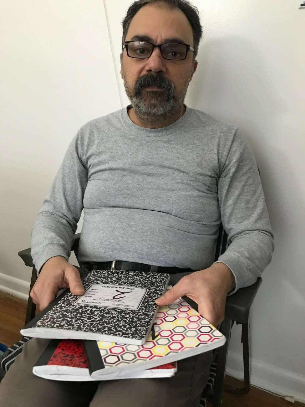 Ahmed Fikry looks over one of his notebooks, written in Arabic, that he filled with stories of his refugee's journey from Baghdad to Syria to Albany.