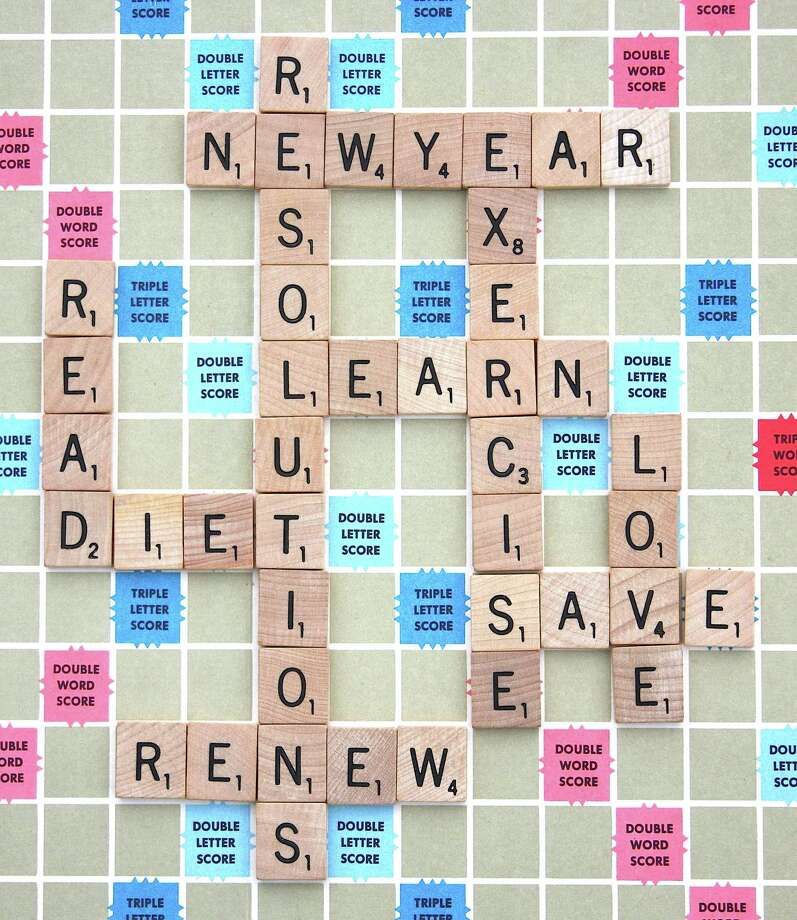 Words that describe various New Year's resolutions are spelled out with lettered wooden tiles on a board game. Photo: Dreamstime