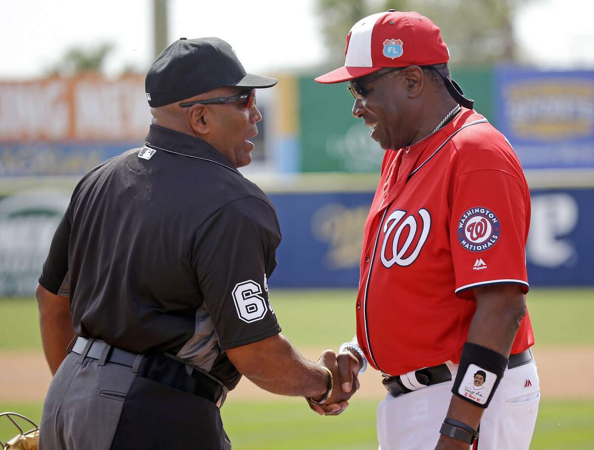 Washington Nationals manager Dusty Baker, right, shakes hands with umpire Laz Diaz before a spring training baseball game against the New York Mets, Thursday, March 3, 2016, in Viera, Fla. (AP Photo/John Raoux)