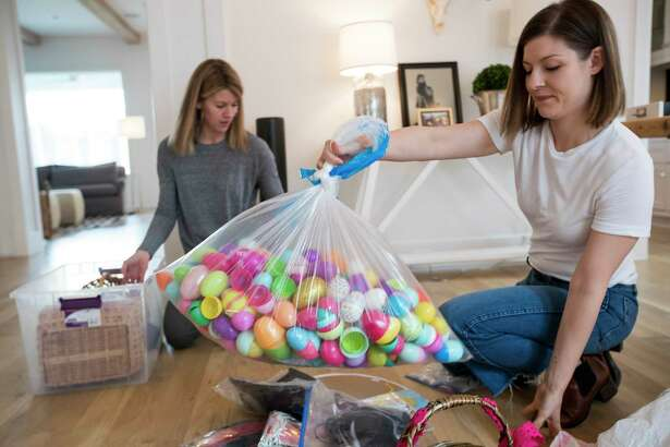 It's time to declutter. Ashley Barber, a Marie Kondo consultant, right, places a bag of plastic eggs to a discard pile as she helps Erica Smith sort out her belongings.