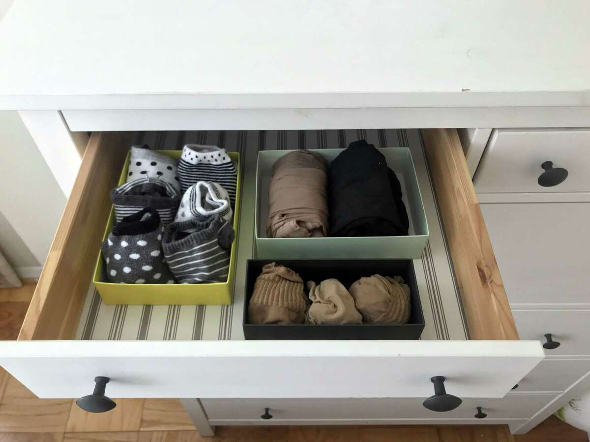 Socks and tights are arranged in a drawer in small boxes, as recommended by Japanese tidying expert Marie Kondo.