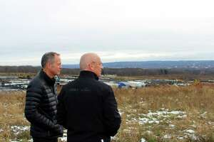 Cree CEO Gregg Lowe, left, looks at the site outside of Utica where the company is building a new $1 billion silicon carbide wafer factory. The company has pledged to employ 600 people in the state.