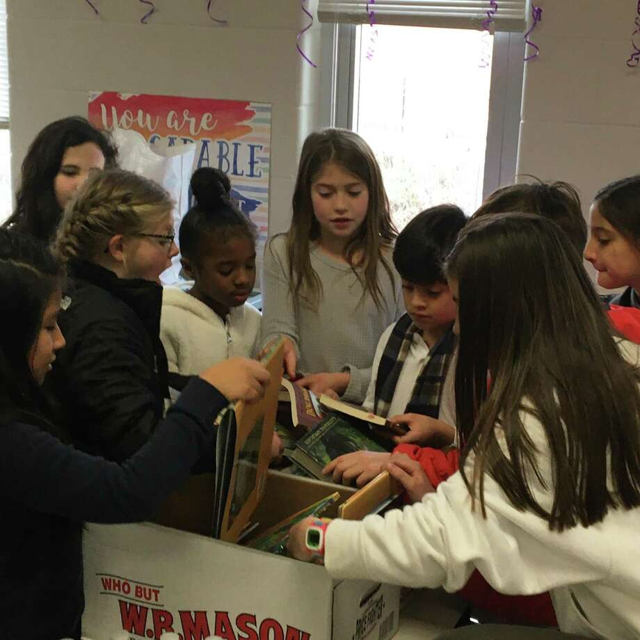 South School students, families and staff in New Canaan recently came together and packed more than 700 meal bags for the Filling In The Blanks warehouse. The students also supported a Holiday Book Drive for Geraldine W. Johnson School in Bridgeport. Photo: Contributed Photo