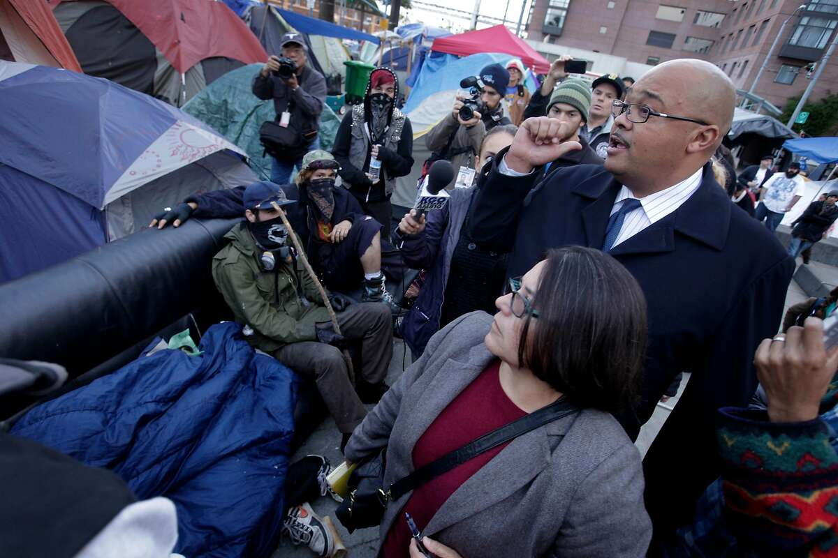 During a walk through of Occupy SF, Barbara Garcia, Director of Health of the Department of Public Health and Mohammed Nuru, Interim Director of the Department of Public Works, tell the people that the couches have to go, Thursday November 17, 2011, at Justin Herman Plaza in San Francisco, Calif.