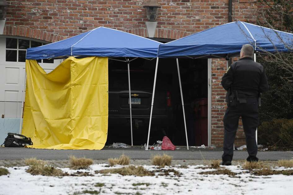 A police officer watches over an area outside of the garage to Fotus Dulos' home, Tuesday, Jan. 28, 2020, in Farmington, Conn. A dispatcher from the Farmington police said officers had responded to Dulos' home and he was later transported to the hospital (AP Photo/Jessica Hill)