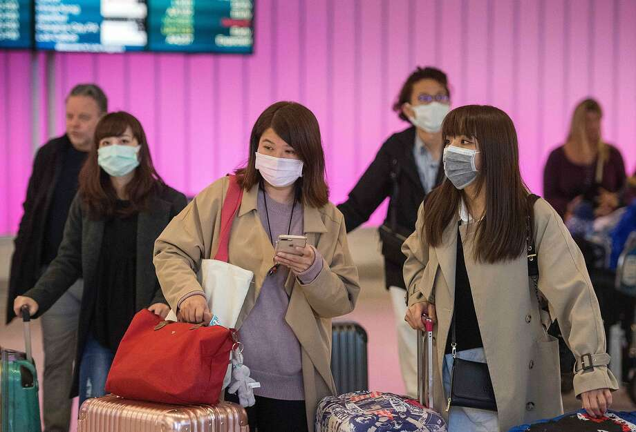"Today United Airlines made a second round of cuts to its China service. In this file photo taken on January 22, 2020 passengers wear protective masks to protect against the spread of the Coronavirus as they arrive at the Los Angeles International Airport, California. - The United States asked China on January 28, 2020 to step up its cooperation with international health authorities over the outbreak of a deadly virus that has claimed more than 100 lives. ""We are urging China -- more cooperation and transparency are the most important steps you can take toward a more effective response,"" Health and Human Services Secretary Alex Azar told reporters. (Photo by Mark RALSTON / AFP) (Photo by MARK RALSTON/AFP via Getty Images) Photo: Mark Ralston / AFP Via Getty Images"
