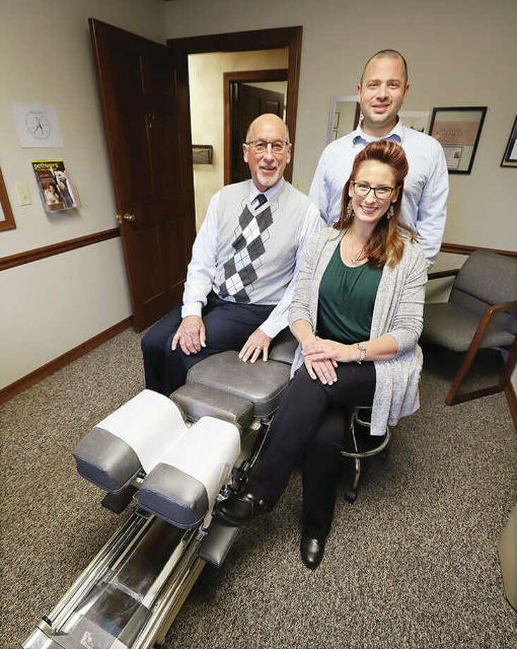 Dr. Frank C. Bemis, left, his daughter, Dr. Kristina E. Bemis Tupman, right, and her husband, Dr. Stephan P. Tupman, standing, at Bemis Tupman Chiropractic, 4105 Humbert Road suite 101, Alton. Dr. Bemis turned over the practice, formerly named Dr. Frank C. Bemis & Associates Chiropractors, in December to the couple, married in 2017. Dr. Bemis began practicing in Alton in 1966 and opened his own business in 1986. Photo: John Badman|The Telegraph