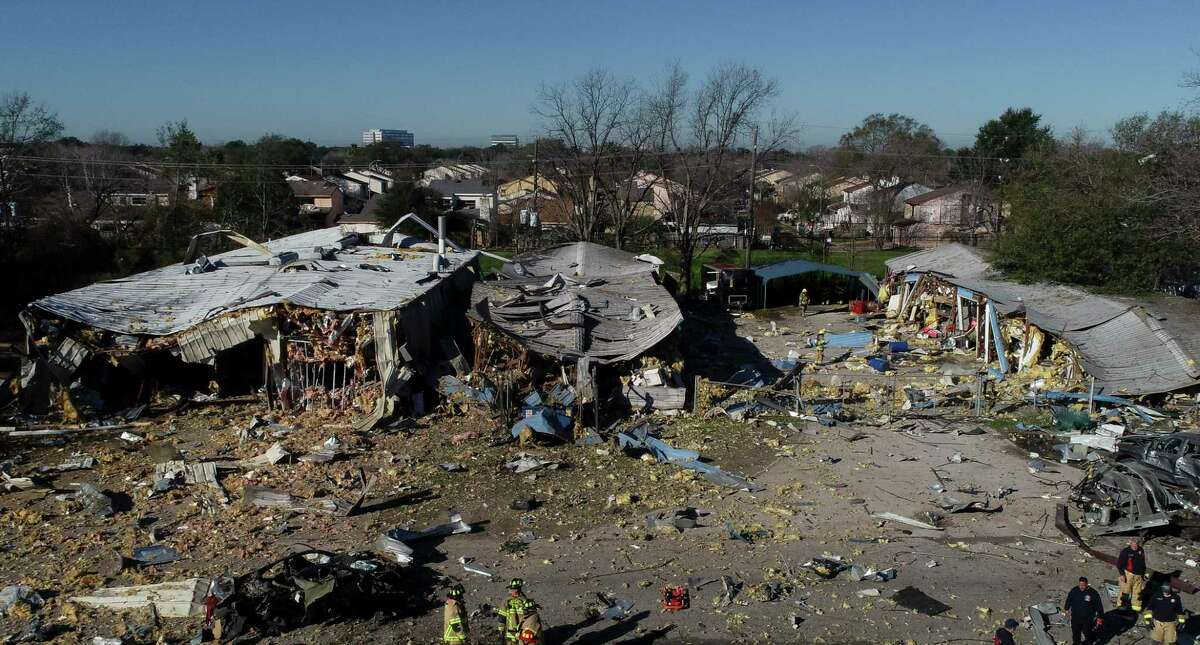 Houston Fire Department firefighters make their way through debris near the site of an explosion at Watson Grinding and Manufacturing on Friday, Jan. 24, 2020. Two people have been reported dead by officials.