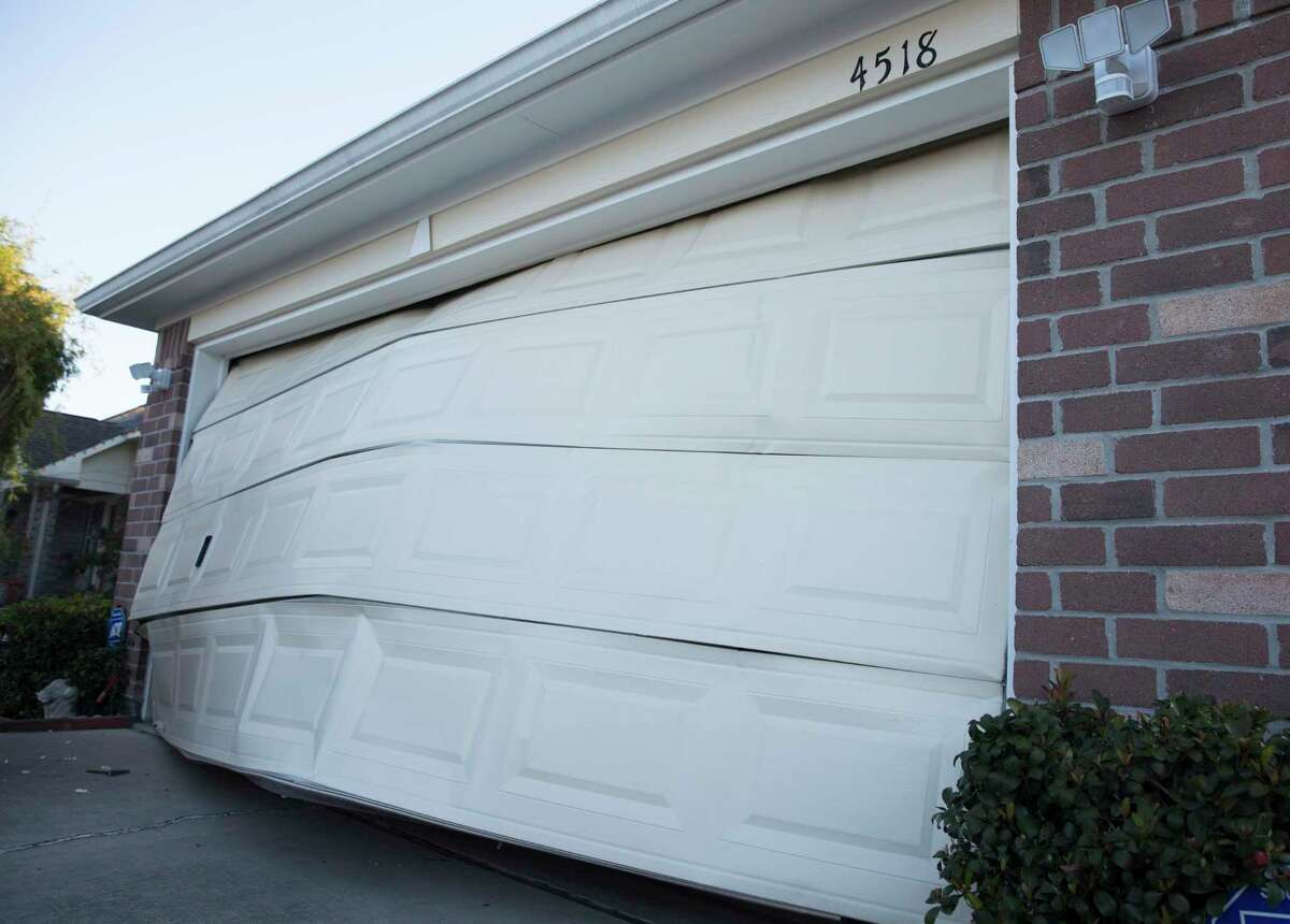 Miguel and Maria Salazar's garage door at Talina Way is distorted by a chemical explosion Friday, Jan. 24, 2020, Spring Branch North neighborhood in Houston. Houston Fire Chief Peña said an explosion happened around 4:30 a.m. at the warehouse of Watson Grinding & Manufacturing Co. on the 4500 block of Gessner Road.