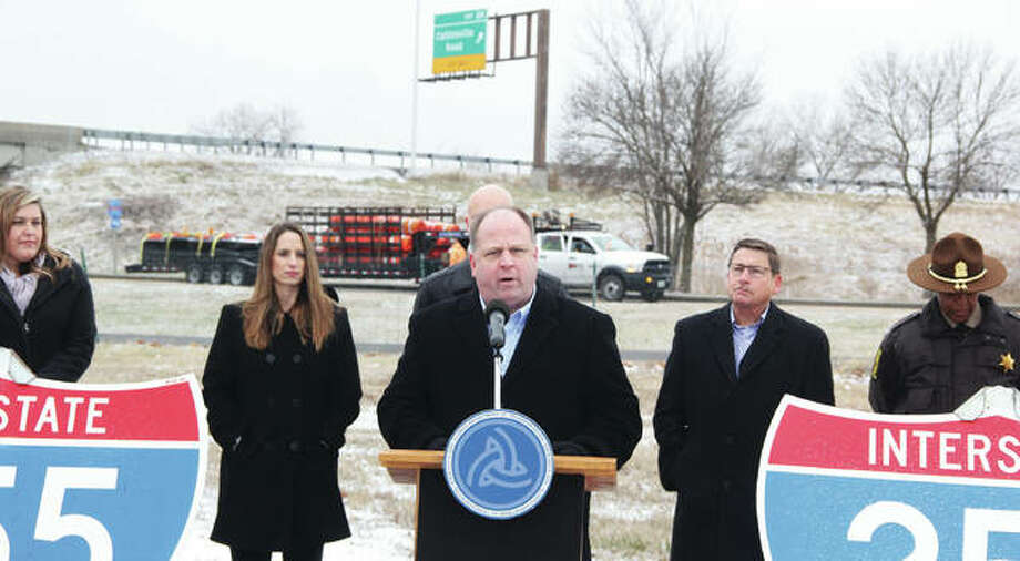 Illinois Department of Transportation spokesman Paul Wappel speaks during a press conference on the upcoming closure of Interstate 255 between I-55/70 and I-64. Behind him a truck hauling construction barricades moves along Collinsville Road as workers pre-position materials for the closure. The interstate will be shut down a total of 10 months for $64 million in rehabilitations and upgrades, diverting about 55,000 vehicles each day.