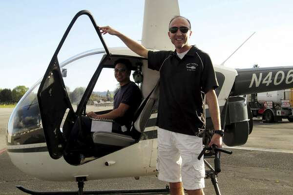 This undated photo provided by Group 3 Aviation shows helicopter pilot Ara Zobayan standing outside a helicopter, at a location not provided. Zobayan was at the controls of the helicopter that crashed in Southern California Sunday, Jan. 26, 2020, killing all nine aboard including former Lakers star Kobe Bryant. The other person inside is unidentified. (Group 3 Aviation via AP)