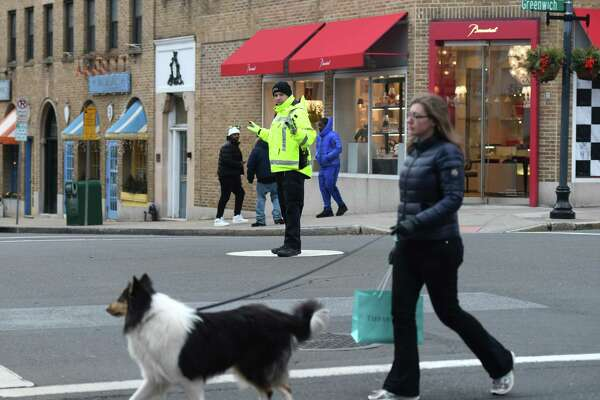 A Greenwich Police Officer directs traffic at the intersection of Greenwich Avenue and Elm Street in Greenwich, Conn. Tuesday, Jan. 28, 2020. First Selectman Fred Camillo proposed the elimination of the longtime tradition of traffic cops along Greenwich Avenue, which he estimated as a cost savings of more than $250,000 per year.