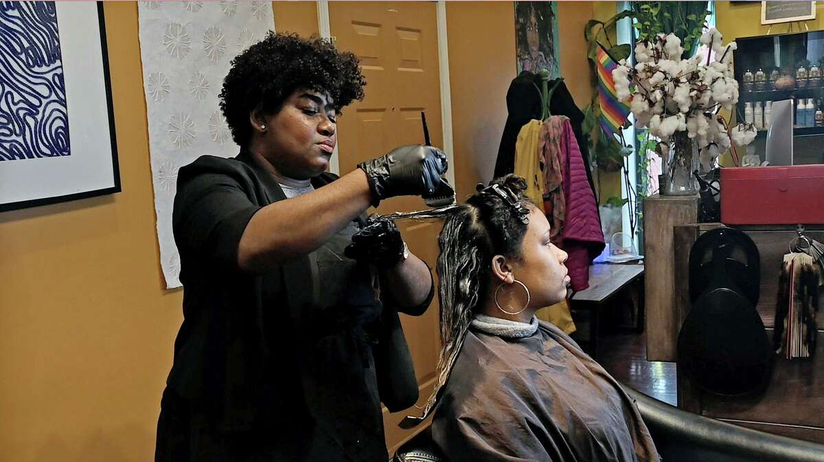 Yasmine Young, owner of Diaspora Salon, styles Mercedes Fernandes' hair. Baltimore City Council is looking to join a growing wave of cities and states in prohibiting discrimination based on hair texture and style.