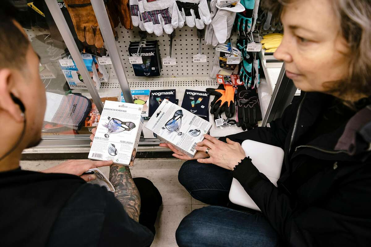Store manager Renato Geslani, left, helps customer Frances Mocnik, who is flying back to her native Sydney, Australia, shop for reusable N95 masks at the downtown Cole Hardware in San Francisco, Calif, on Tuesday, January 28, 2020.