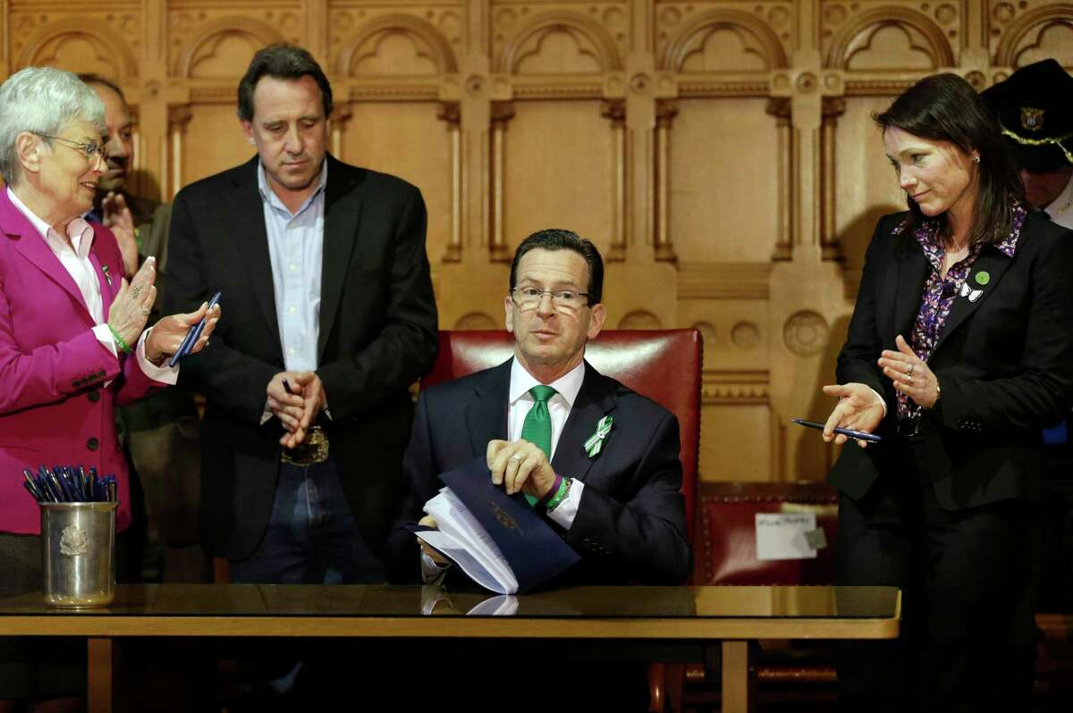 Connecticut Gov. Dannel P. Malloy, center, completes signing legislation at the Capitol in Hartford, Conn., Thursday, April 4, 2013, that included new restrictions on weapons and large capacity ammunition magazines, a response to last year's deadly school shooting in Newtown. Neil Heslin, second from left, father of Sandy Hook shooting victim Jesse Lewis, Nicole Hockley, right, mother of Sandy Hook School shooting victim Dylan, and Conn. Lt. Gov. Nancy Wyman, left, applaud.