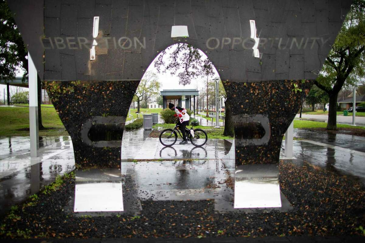 A person riding a bike is framed by a sculpture that stands at the Hutchins Street entrance of the Emancipation Park on Tuesday, Jan. 28, 2020, in Houston.