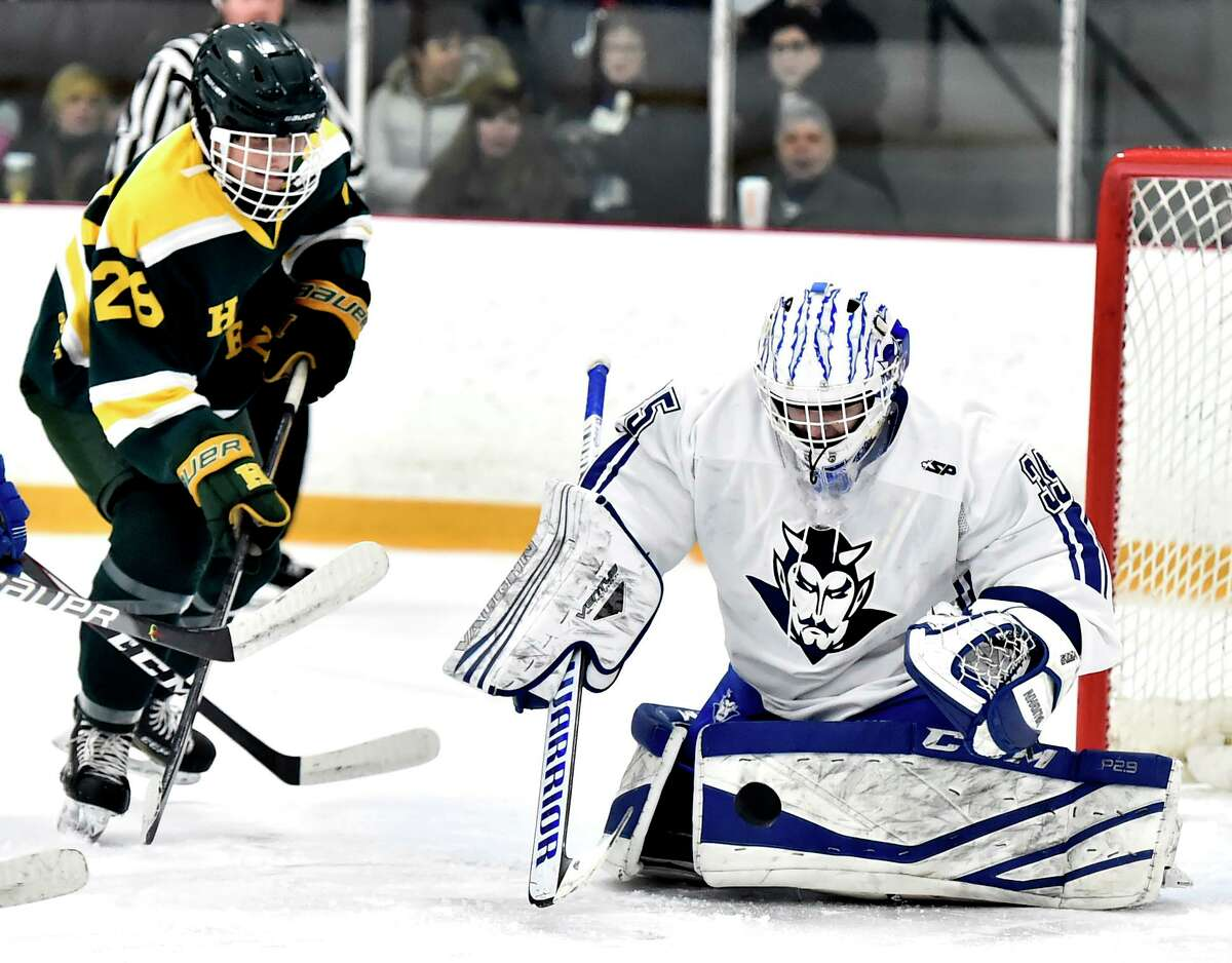 Hamden's, left, watches the puck bounce off of West Haven goalie Jared Pliszka during a game earlier this season.