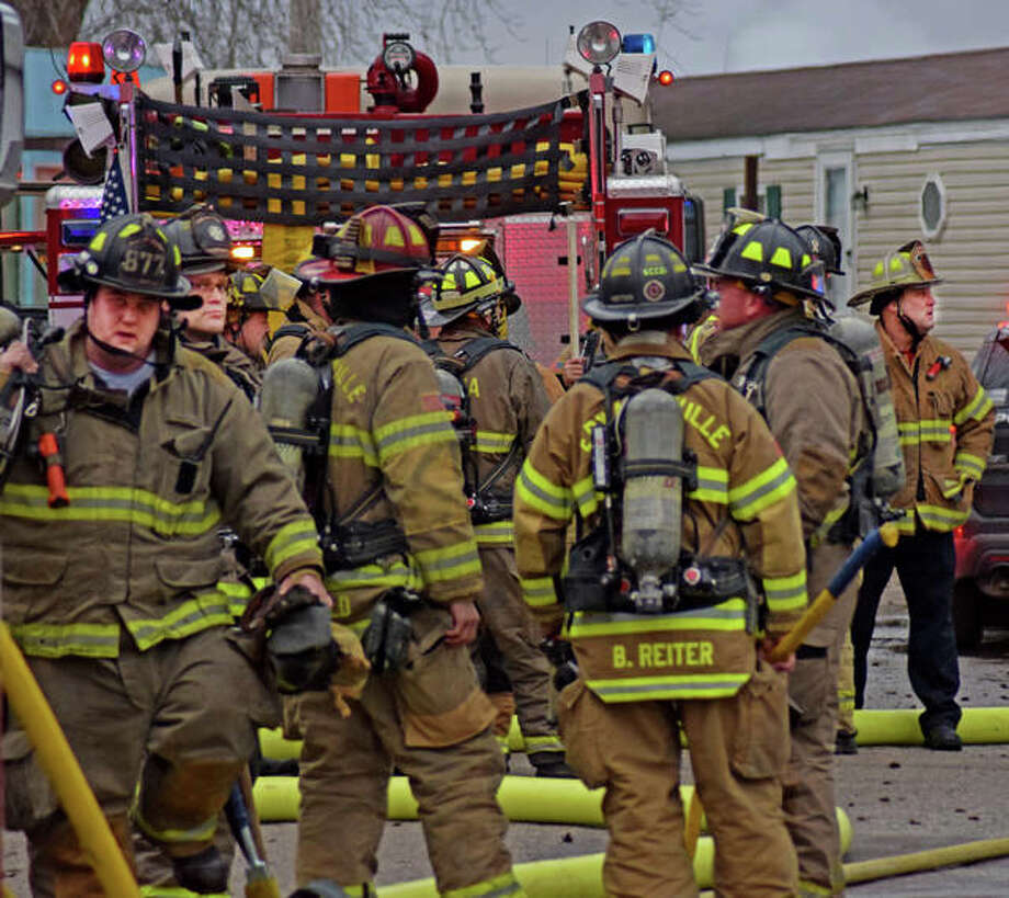 Firefighters rest and talk with one another after battling a blaze for about 30 minutes. Photo: Tyler Pletsch | The Intelligencer