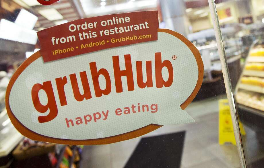 In this file photo, a sign with the old GrubHub logo is displayed is displayed on the door to a New York restaurant. Photo: Mark Lennihan / Associated Press 2014