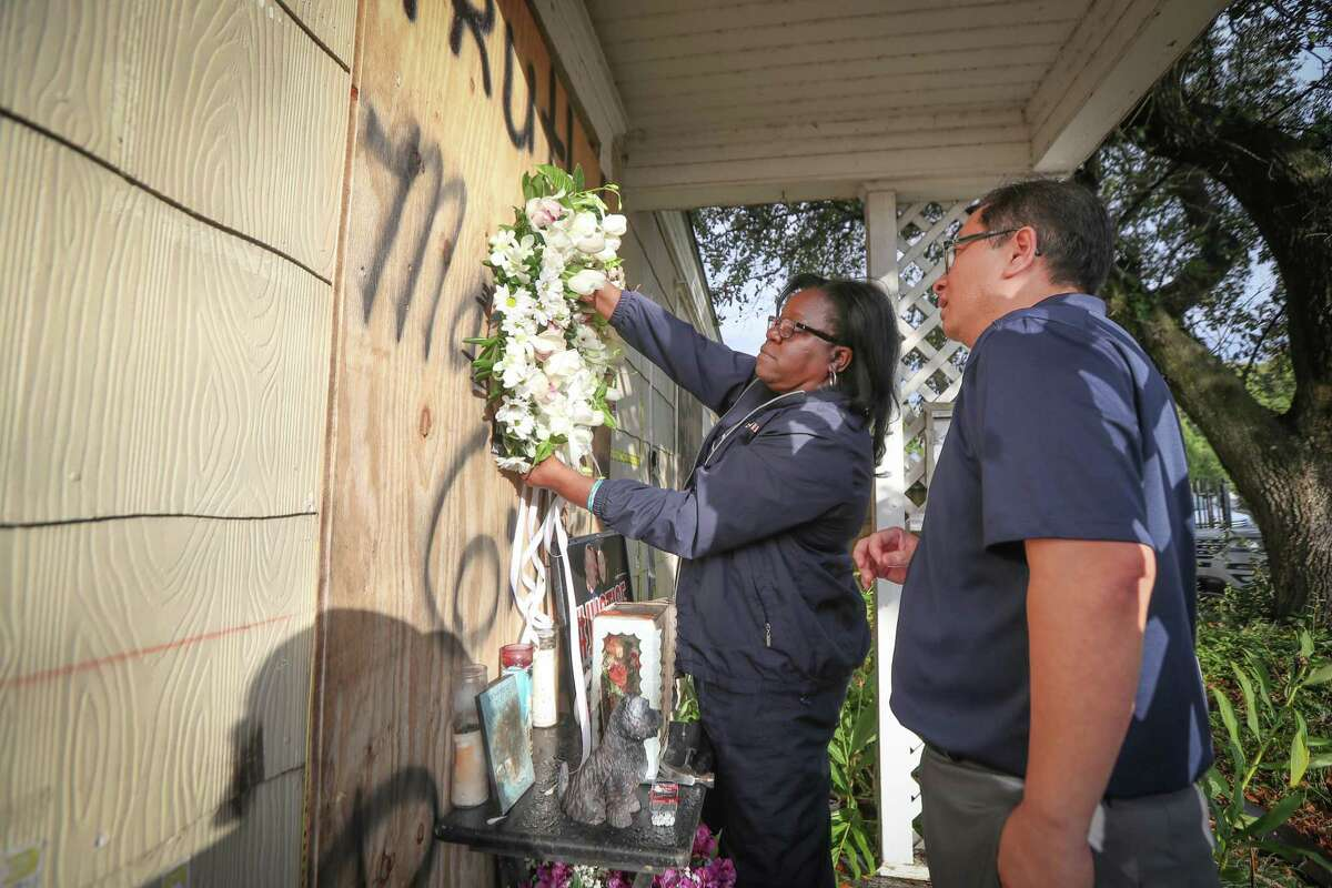 Former Houston Police Officer Kathy Swilley and We The People Founder Hai Bui attempt to hang a wreath on a house at 7815 Harding Street before a small vigil on anniversary of botched raid Tuesday, Jan. 28, 2020, in Houston.