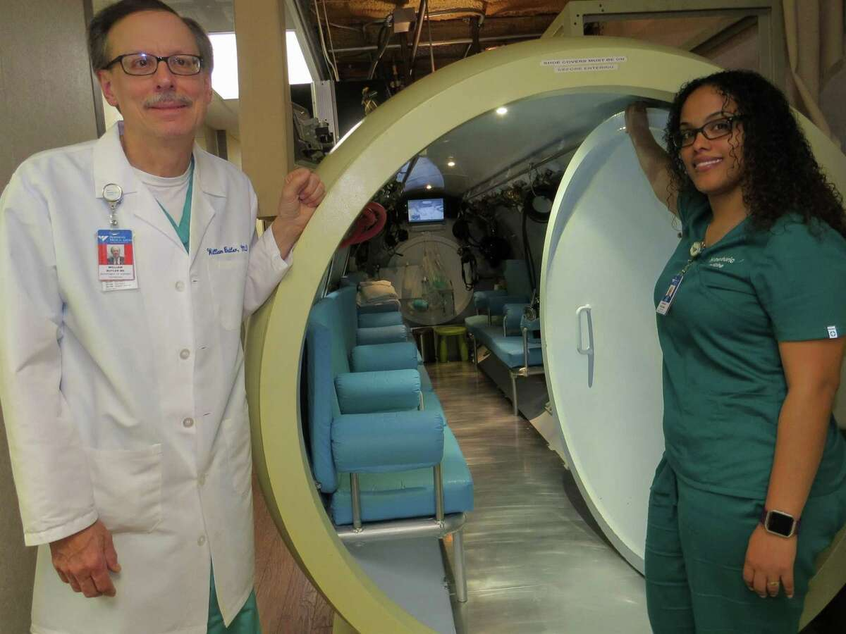 In this undated file photo William Butler and hyperbaric technician Aidaliz Vizcaino stand outside the door of Bridgeport Hospital's hyperbaric oxygen therapy chamber.