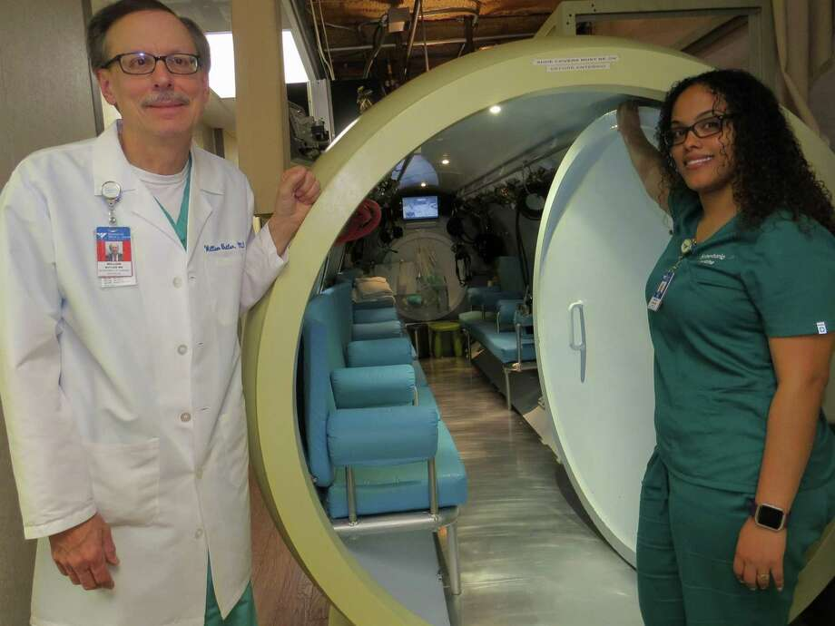 In this undated file photo William Butler and hyperbaric technician Aidaliz Vizcaino stand outside the door of Bridgeport Hospital's hyperbaric oxygen therapy chamber. Photo: Contributed Photo / Bridgeport Hospital