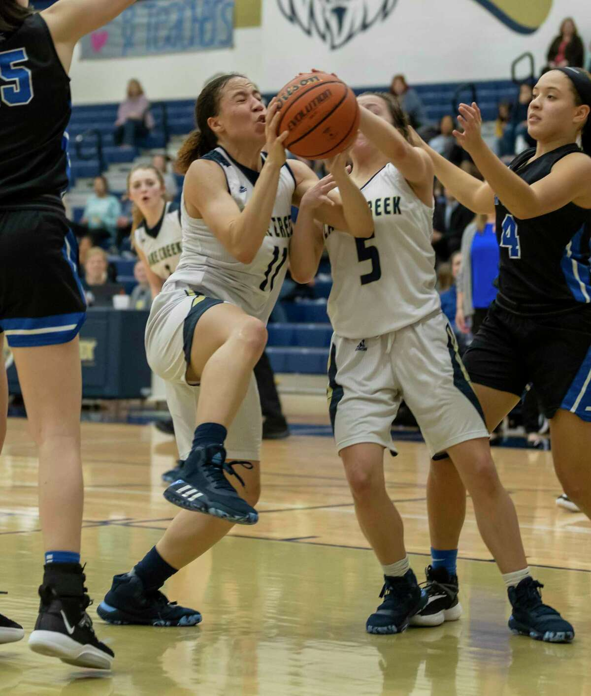 Lake Creek forward Jasmine Payne (11), Lake Creek guard Kennedy Oliver (5) and New Caney guard Jasmine Toney (4) fight for a rebound during the first half in a District 20-5A game at Lake Creek high school, Tuesday, Jan. 28, 2020.
