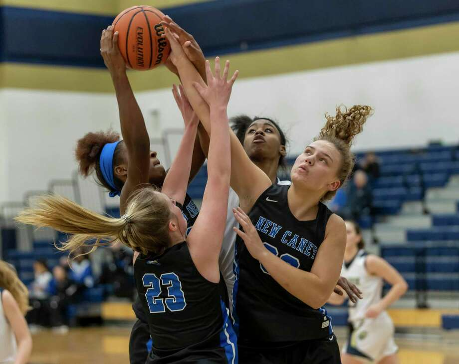 New Caney power forward Mickayla Leftridge (22), New Caney center Skyler Richardson (23), New Caney power forward Abigail Lynch (30) and Lake Creek guard Taliyah McShan (15) fight for a rebound during the second half in a District 20-5A game at Lake Creek high school, Tuesday, Jan. 28, 2020. Photo: Gustavo Huerta, Houston Chronicle / Staff Photographer / Houston Chronicle