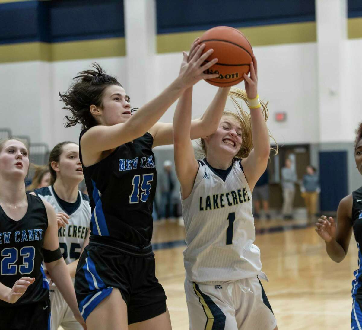 Lake Creek shooting guard Makenzie Logeman (1) and New Caney power forward Micha Mize (15) fight for a rebound during the second half in a District 20-5A game at Lake Creek high school, Tuesday, Jan. 28, 2020.