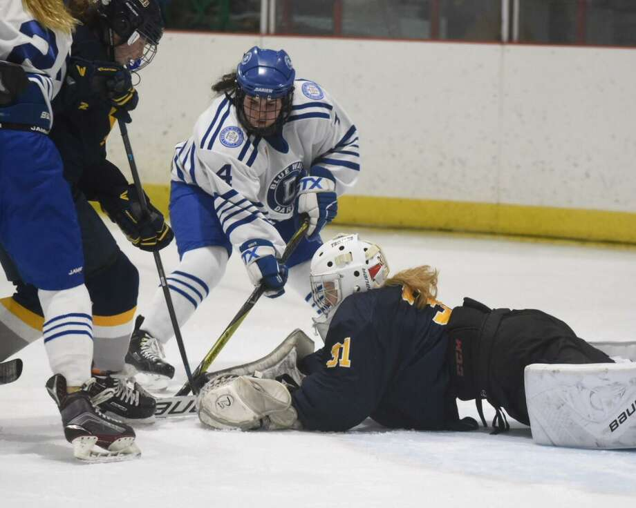 Simsbury goalie Kaitlyn O'Brien (31) dives out to make a stop in front of Darien's Olivia Toscano (4) during a girls ice hockey game at the Darien Ice House on Tuesday, Jan. 29, 2020. Photo: David Stewart / Hearst Connecticut Media / Connecticut Post