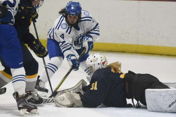 Simsbury goalie Kaitlyn O'Brien (31) dives out to make a stop in front of Darien's Olivia Toscano (4) during a girls ice hockey game at the Darien Ice House on Tuesday, Jan. 29, 2020.