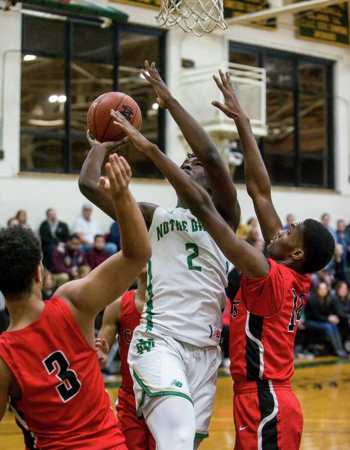 Notre Dame-West Haven's Amadou Kamara goes up for a shot against Wilbur Cross defenders Darius Esdaile (3) and Daquan Goodwin on Tuesday. Photo: John Vanacore / For Hearst Connecticut Media